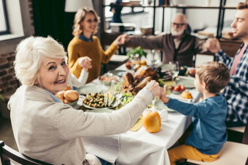family holding hands and praying on thanksgiving before stock photo