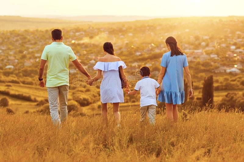 Family holding hands walking in nature at sunset. royalty free stock image