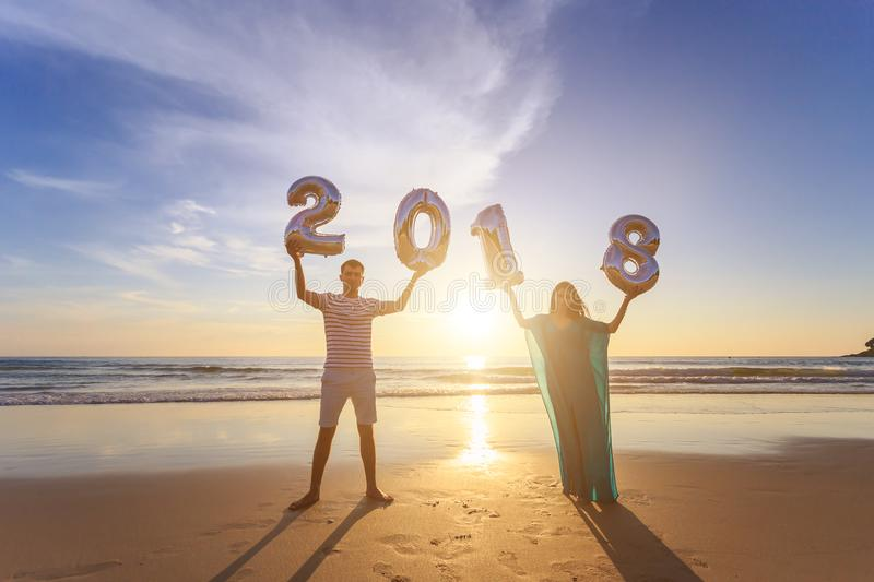 Family holding number balloon 2018 on the beach at the sunset ti. Silhouette of family holding number balloon 2018 on the beach at the sunset time. Outdoor stock image