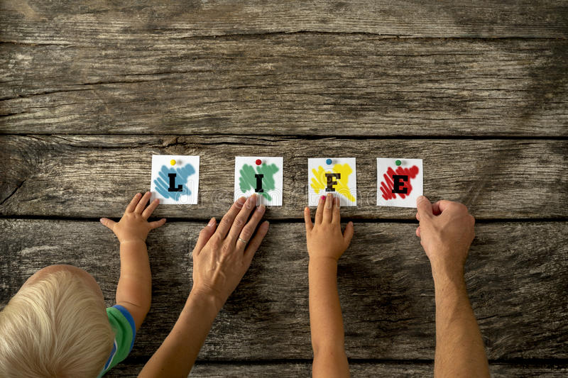 Family Holding Paper on Table for Life Concept. High Angle View of Hands of Family Holding Small Pieces of Colored Paper Together on Top of a Rustic Table For royalty free stock photo