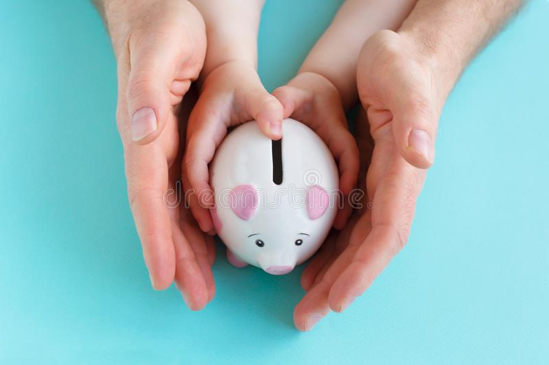 Family holding piggybank in hands. Investment concept royalty free stock photography