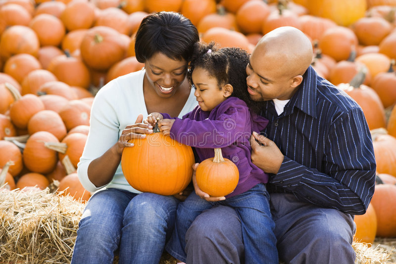 Family holding pumpkins. Happy smiling family sitting on hay bales and holding pumpkins at outdoor market stock images