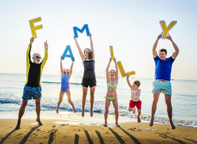 Family holding up letters at the beach stock images