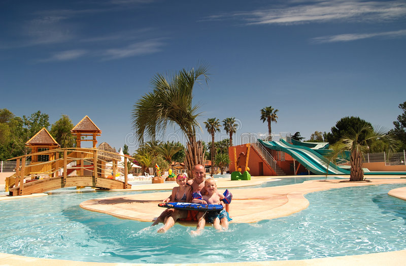 Family holiday. Dad and children having fun on the swimming pool royalty free stock photos