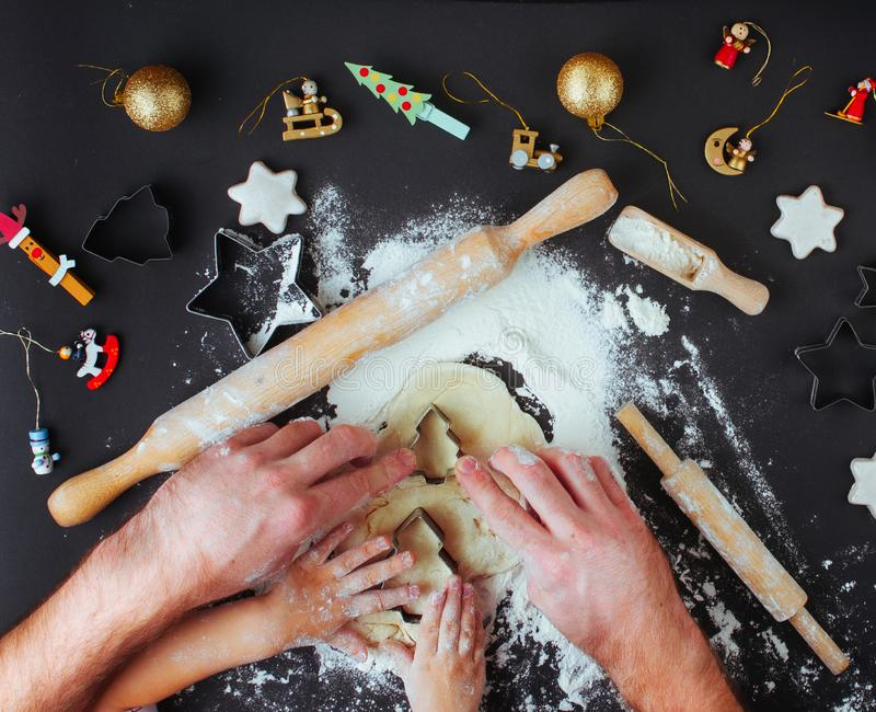 Top view of fathers and kids hands making Christmas cookies on b. Family holiday activity. Top view of father`s and kid`s hands making Christmas cookies on black royalty free stock photography