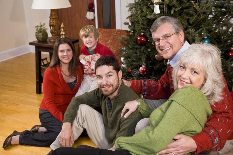 Family holiday gathering by Christmas tree stock photo