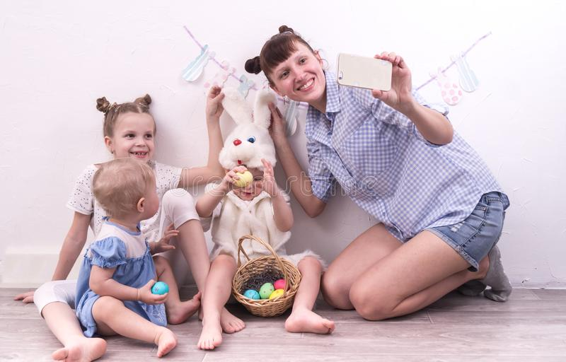 Family holiday: Mother with children celebrates Easter and makes selfie on smartphone stock photo