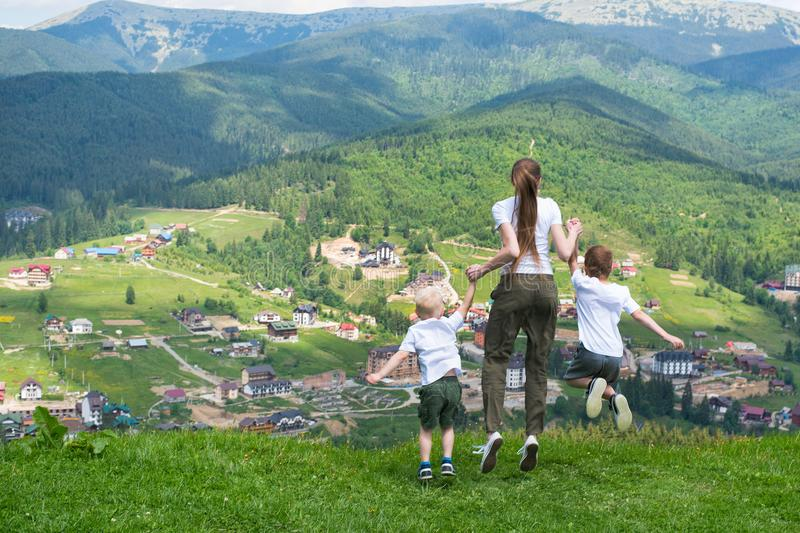Family holiday. Mother with sons jump on the background of mount royalty free stock photos