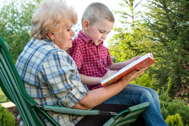 Grandmother and grandson reading a book outdoors.Family holiday with my grandmother. royalty free stock photo