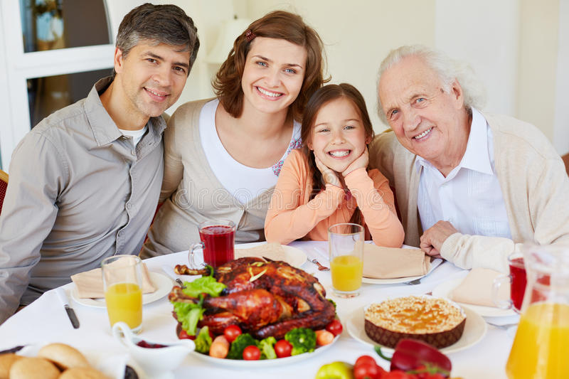Family holiday. Portrait of happy family members sitting at festive table on Thanksgiving day and looking at camera stock photo