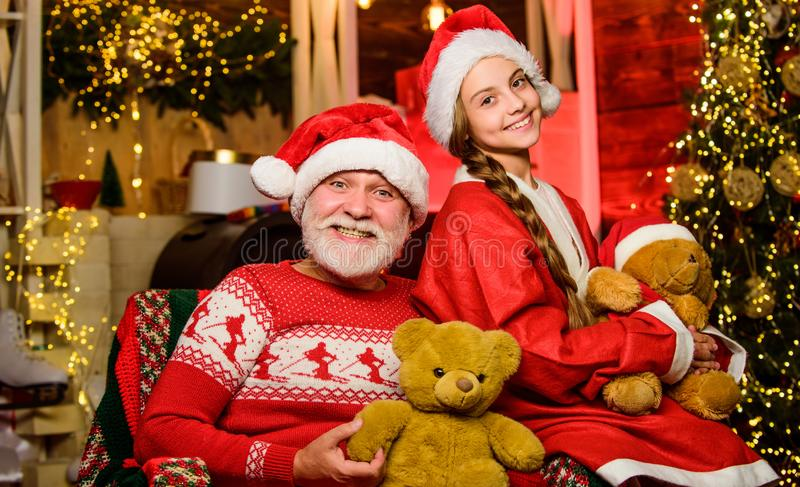 Family holiday weekend. Little girl with santa man. grandpa and grandchild at home. happy new year. never much toy royalty free stock photos