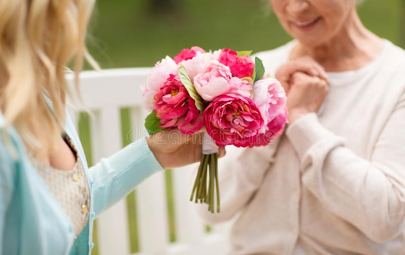 Daughter giving flowers to senior mother at park royalty free stock images