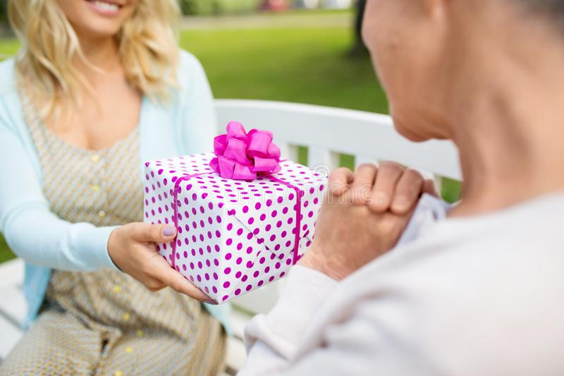 Daughter giving present to senior mother at park royalty free stock images