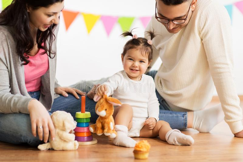 Baby girl with parents playing with toy rabbit royalty free stock photo