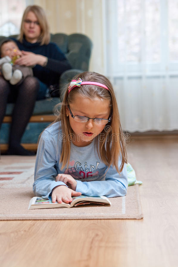 Family at home. Family scene at home, girl reads on carpet while mother holds baby in the background stock photo