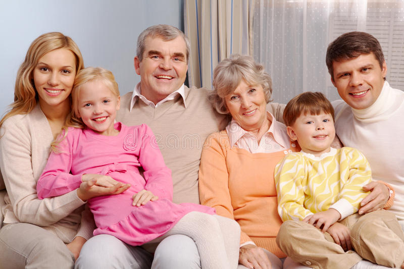 Family at home. Portrait of senior and young couples with their children sitting on sofa at home royalty free stock image