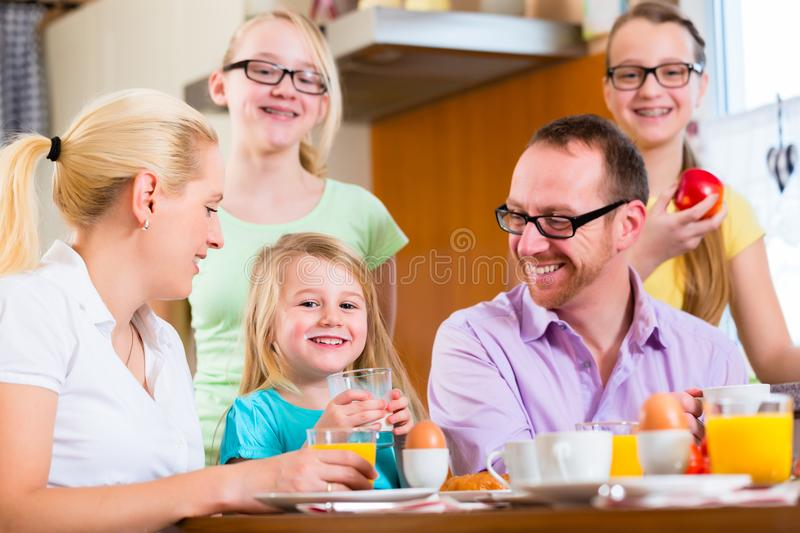 Family at home having breakfast in kitchen. Family in their home having breakfast with eggs, fruit, coffee and juice royalty free stock images