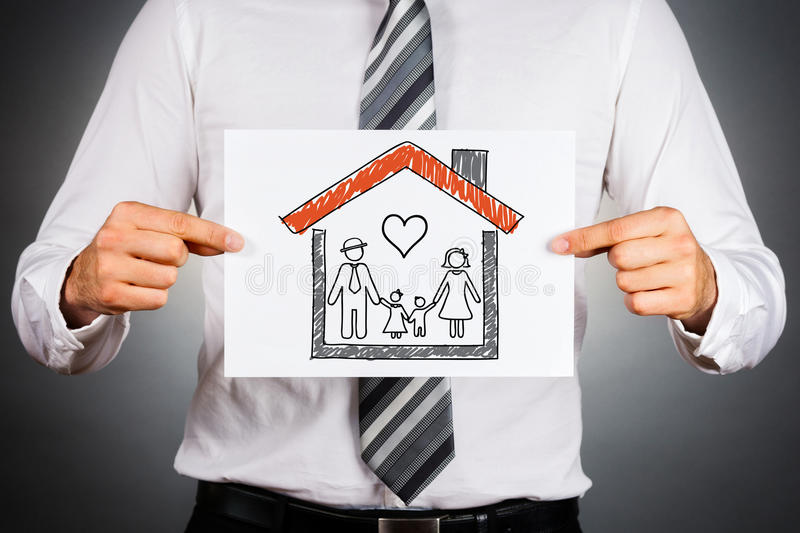 Family and home insurance concept. Businessman holding paper with drawing of a family, inside family home stock images