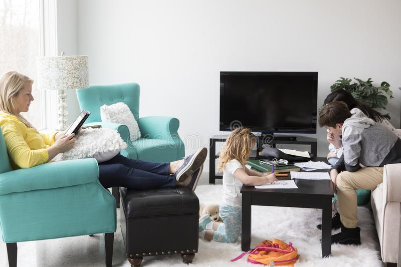 Family at Home. Family relaxing and doing homework in their living room stock photo
