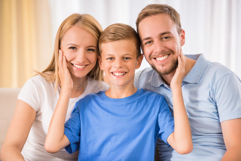 Family at home. Young happy parent and their teenage son are posing at home, smiling royalty free stock photos