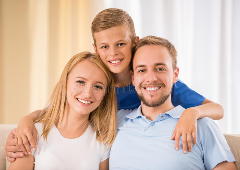 Family at home. Young happy parents and their teenage son are posing at home, smiling stock photography