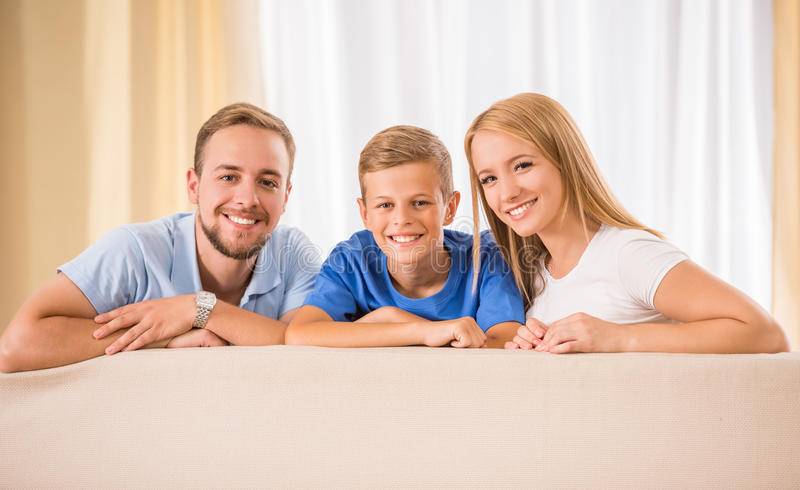 Family at home. Young happy parents and their teenage son are posing at home, smiling stock image