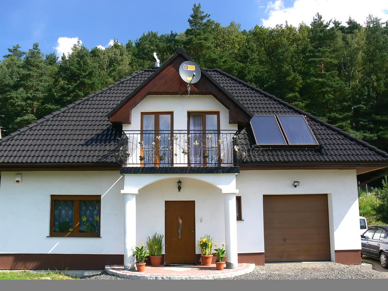 Family house. New beautiful white family house with garage and solar panels on the black tiled roof royalty free stock photo