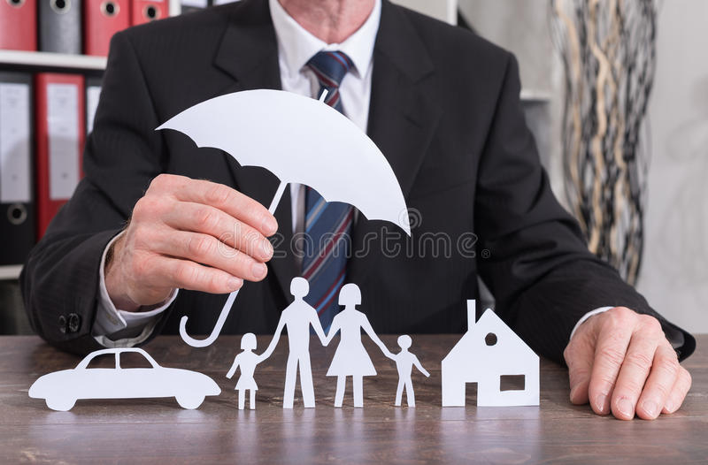 Family, house and car insurance concept. House, car and family protected with an umbrella by an insurer - insurance concept royalty free stock photo