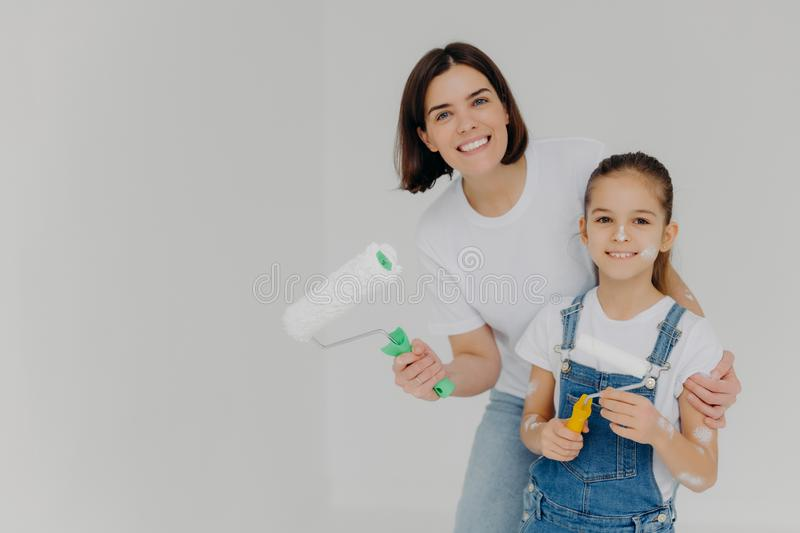 Family and house repairing concept. Positive caring mother cuddles child, have fun when refurbish walls, dressed in casual royalty free stock image