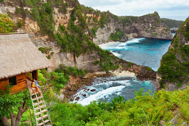 Family in house on tree at Atuh beach, Nusa Penida. Happy family travel lifestyle. Mother with child sit on steps of traditional house on tree, look at Atun royalty free stock photography