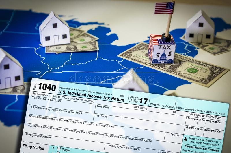 Family houses with dollar bills and central goverment tax over a US map stock photo