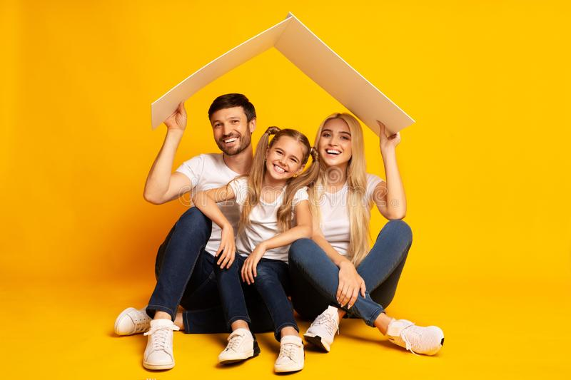 Family Housing. Parents And Daughter Sitting Under Roof, Studio Shot royalty free stock images