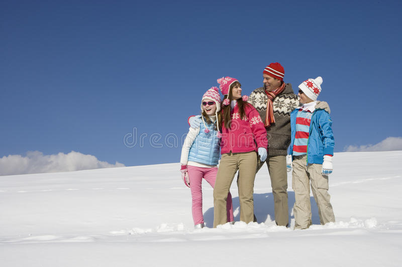 Family hugging and standing in snow royalty free stock images