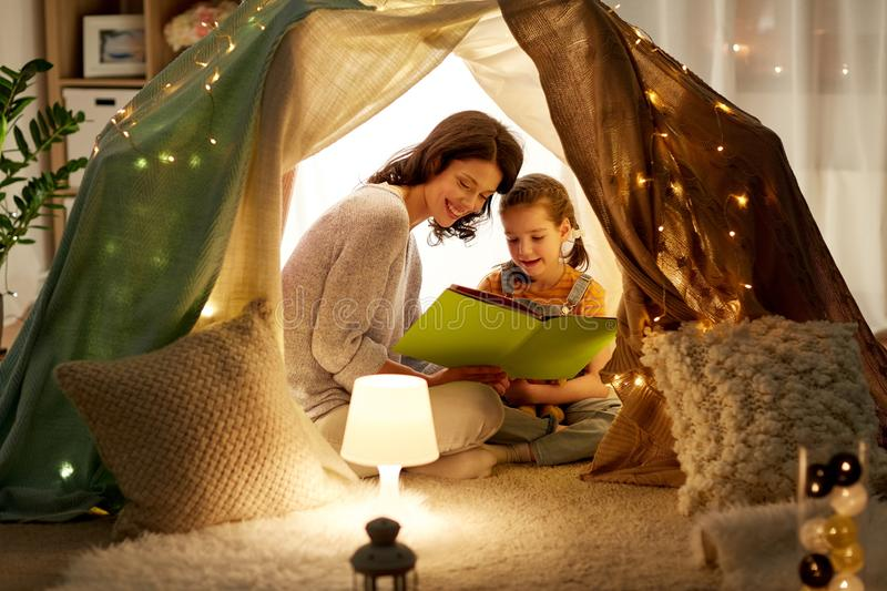Happy family reading book in kids tent at home stock photo