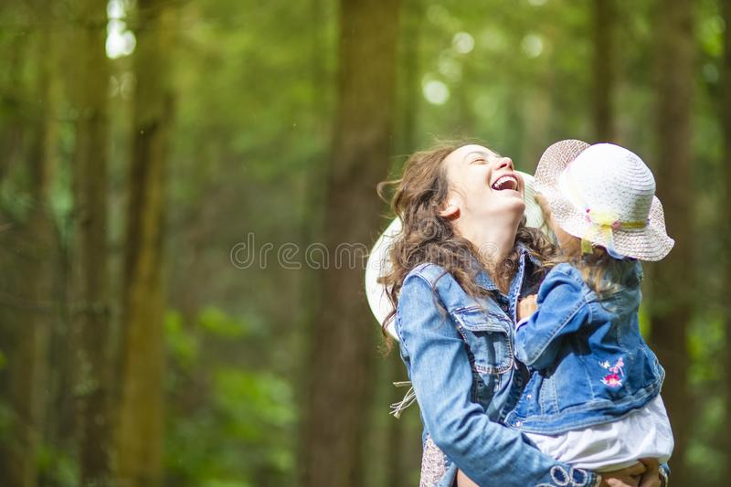 Caucasian Mother with Her Little Daughter Posing Together in Green Summer Forest. Family Ideas. portrait of Happy and Laughing Caucasian Mother with Her Little stock photos
