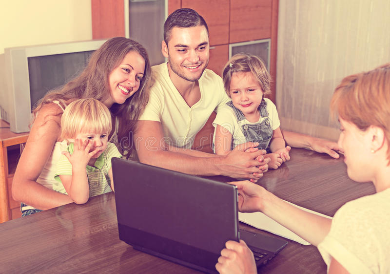 Family with insurance agent. Insurance agent consulting happy young family with kids at home. Focus on woman royalty free stock image