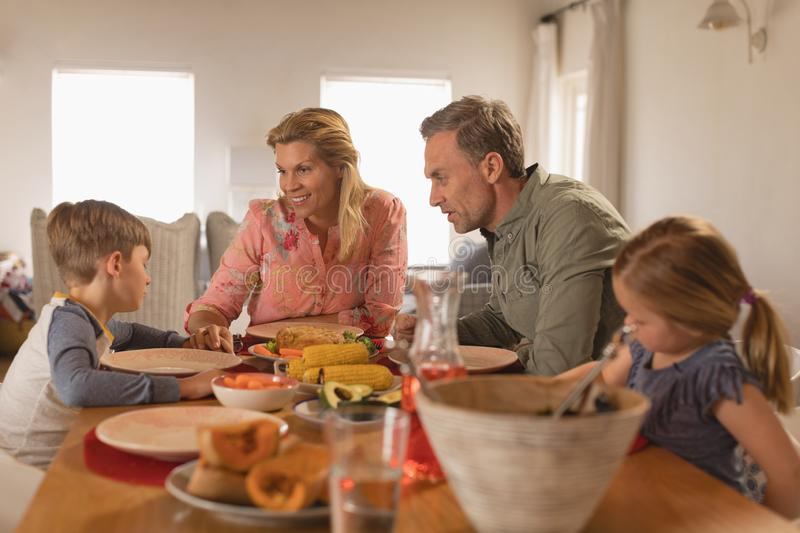 Family interacting with each other while having food on dining table stock photo