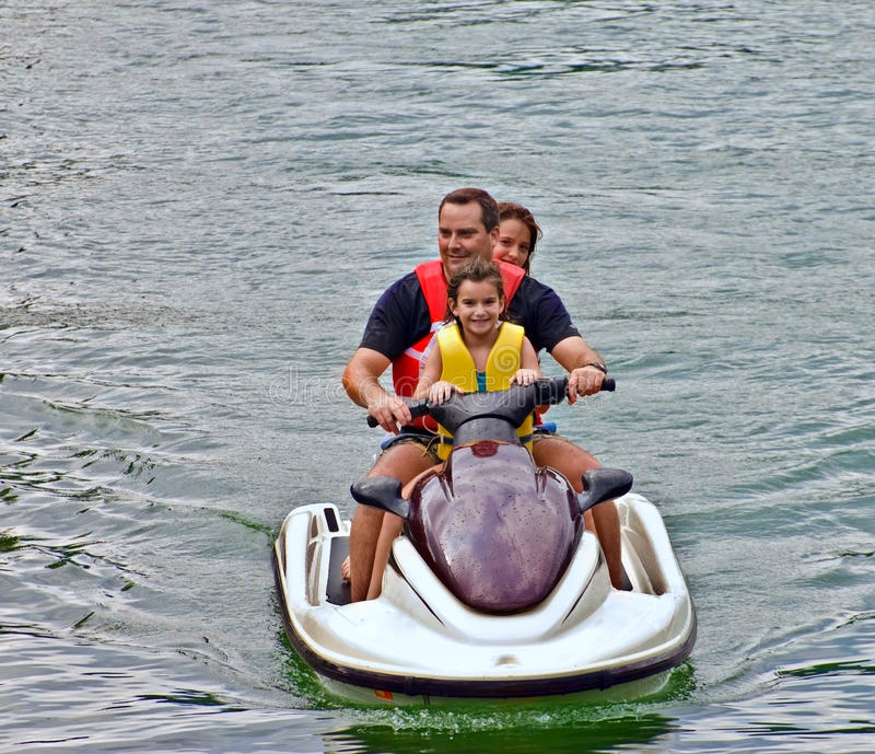Family on a Jet Ski. A man and his daughters riding a jet ski