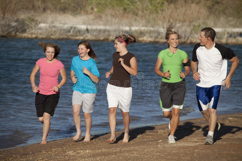 Family jogging together. A mother and father running with their girls having a good time at the beach stock photos
