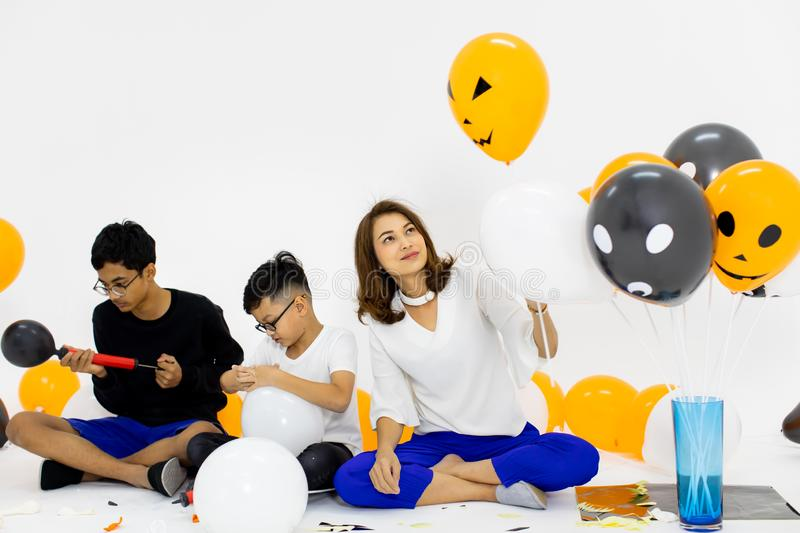 Family join together for preparing fancy balloon for party. Concept for funny activity in halloween festival.  stock photography