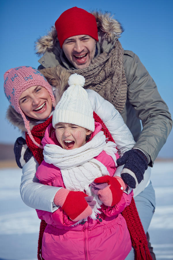 Family joy. Joyful family of father, mother and daughter in winterwear royalty free stock photos