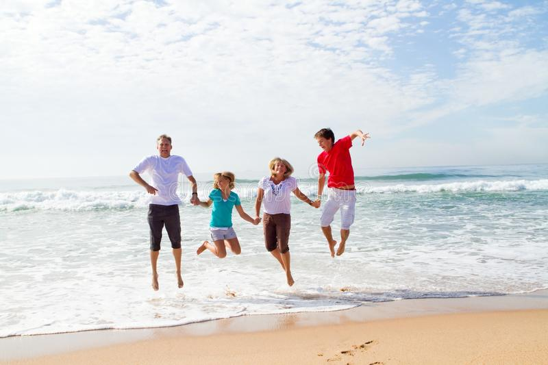 Family jumping on beach royalty free stock photography