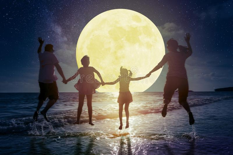 Family jumping on beach and watching the moon.Celebrate Mid autumn festival concept stock images