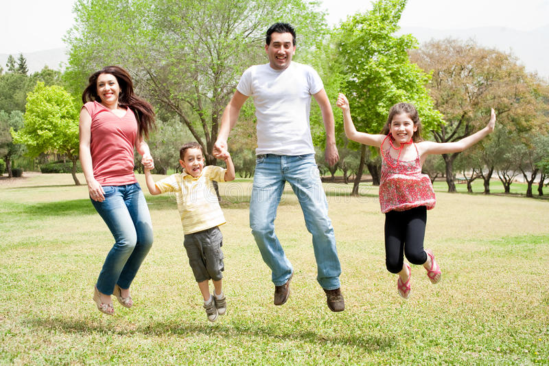 Family jumping together in the park royalty free stock photos