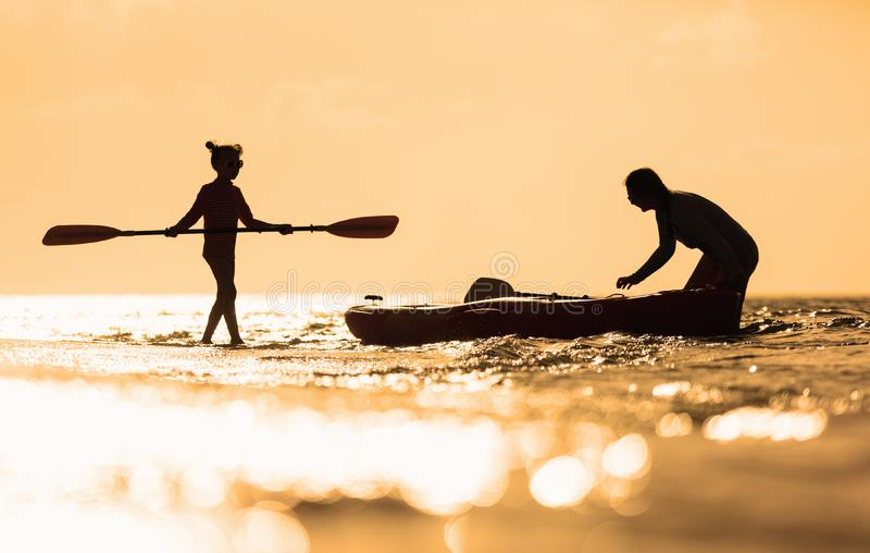 Family kayaking at sunset. Silhouettes family of mother and daughter paddling on kayak at tropical ocean at sunset stock photos