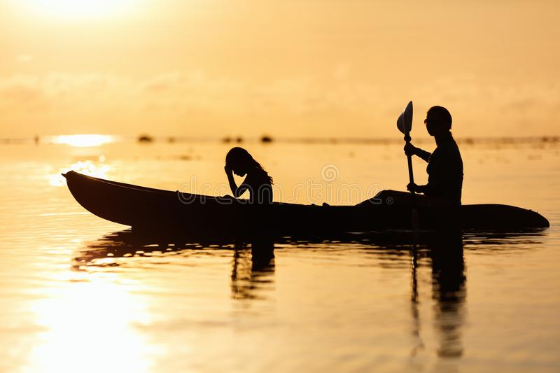 Family kayaking at sunset. Silhouettes family of mother and daughter paddling on kayak at tropical ocean at sunset stock photography