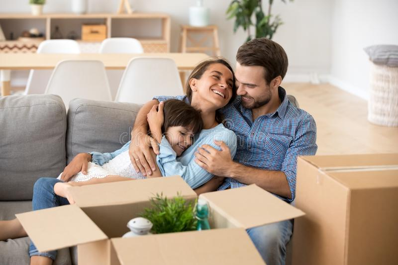 Family with kid embracing on sofa moving in new home. Happy mom dad with kid daughter embracing smiling relaxing on couch after relocation move in new home stock photos