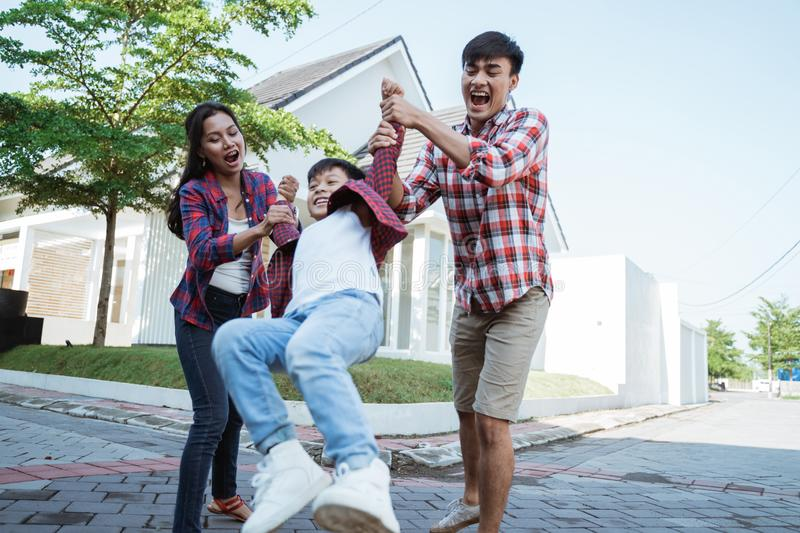 Family and kid enjoy playing together in front of their house stock images