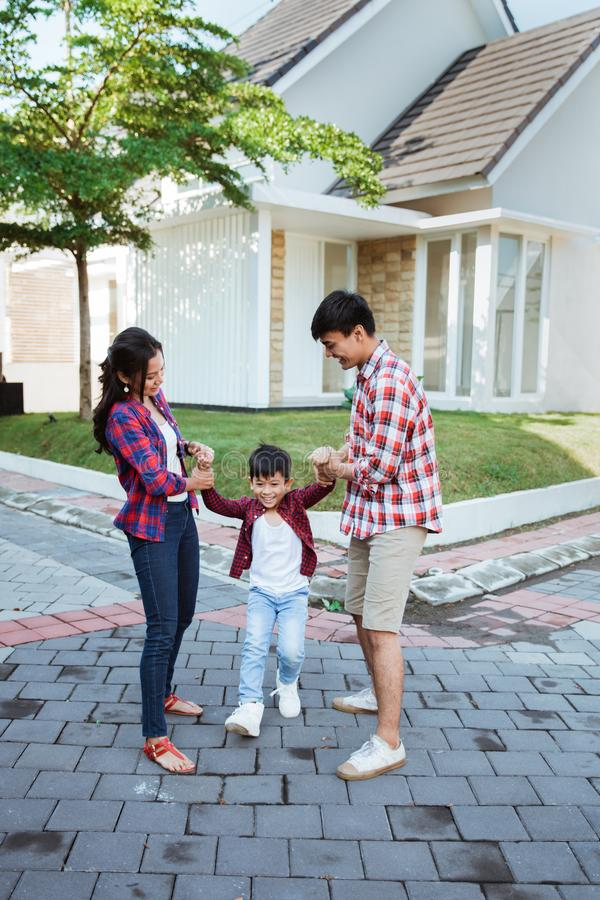 Family and kid enjoy playing together in front of their house stock photos