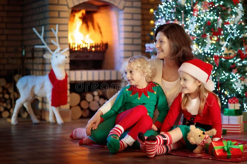 Family with kids at Christmas tree and fireplace. Mother and children opening gifts at fire place. Boy, girl and mom open presents. Winter holidays interior stock image